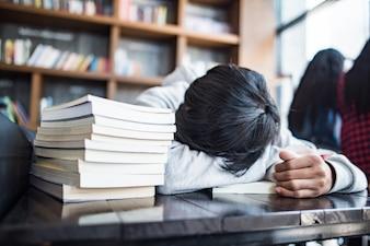 Lo studente barbuto addormentato del giovane si trova sulle mani in caffè