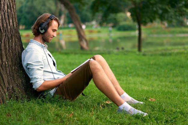 Lo studente con le cuffie in parco della città universitaria ha letto un libro