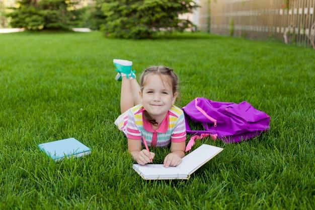 Lo studente della scuola elementare della scolara della ragazza del bambino che si trova sull'erba ed assorbe un taccuino. concetto di nuovo a scuola. attività all'aperto