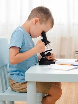 Lo studente è seduto a tavola e impegnato in materiale didattico. lo scolaro guarda attraverso un microscopio.