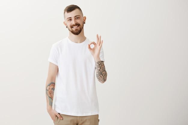 Lo studente maschio soddisfatto felice che mostra il gesto giusto, consiglia il promo