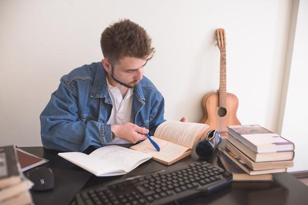 Lo studente seduto a casa al computer legge libri ed esegue un compito a casa.
