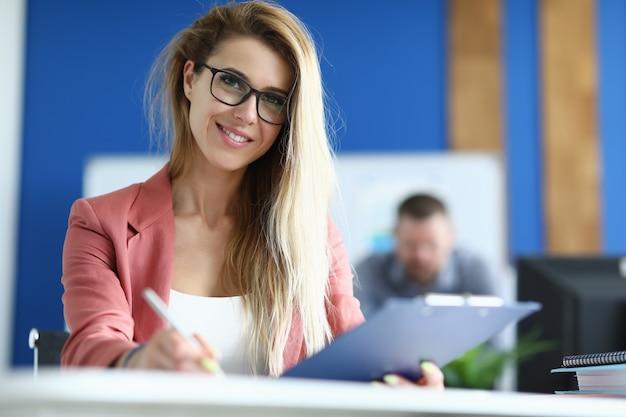 Lo studente tiene la penna in una mano e la cartella nell'altra in classe e segue la formazione.