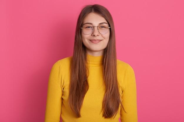 Lo studio dell'interno ha sparato degli occhiali da portare attraenti della bella giovane donna graziosa e della felpa gialla, avendo capelli biondi lunghi, posando isolato sopra la parete rosa. concetto di persone ed emozioni.