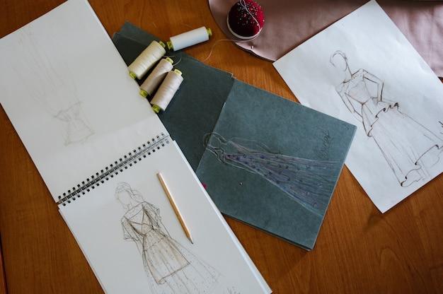 Lo studio dello stilista con attrezzatura per cucire e lo schizzo progettano sulla tavola di lavoro, concetto di sartoria