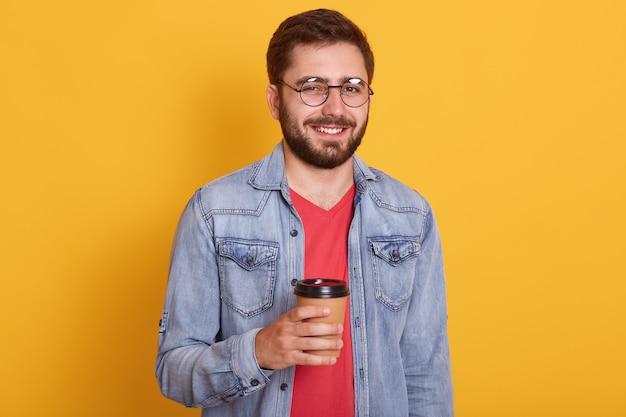 Lo studio ha sparato al giovane attraente con barba e capelli scuri, con felice espressione facciale, tenendo in mano una tazza di caffè o tè, abiti eleganti giacca di jeans e camicia rossa