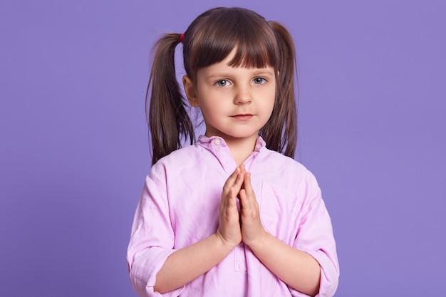 Lo studio ha sparato del piccolo bambino femminile affascinante che porta la camicia pallida delle rose