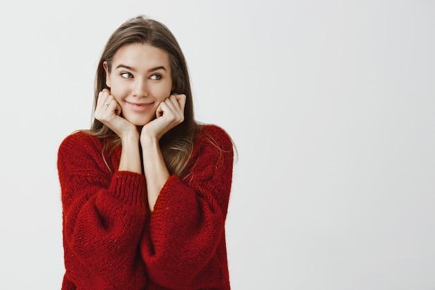 Lo studio ha sparato di felice carino collega femmina indoeuropea in elegante maglione sciolto, appoggiandosi sulle mani e guardando da parte con curioso sorriso allegro, essendo di buon umore, aspettando il suo ordine al ristorante