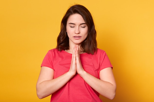 Lo studio sparato della femmina caucasica prega per il benessere della sua famiglia, tiene le palme premute insieme, pone nel gesto di preghiera con gli occhi vicini contro il giallo