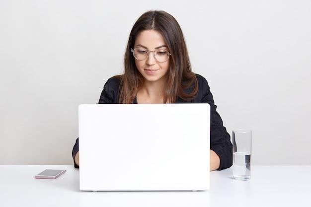 Lo sviluppatore di software femminile professionale lavora su un computer portatile, informazioni sulle tastiere, collegato a internet wireless, funziona con gadget moderni, beve acqua, isolato sul muro bianco dello studio