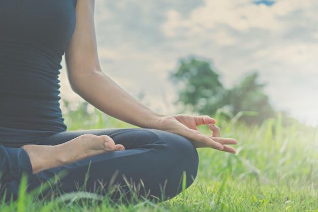 Lo yoga della donna si distende sulla natura.