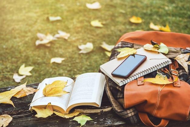 Lo zaino è posizionato su un antico tavolo di legno con libri, quaderni, telefoni e la natura delle foglie di acero dalla vista dall'alto.