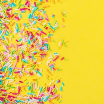 Lo zucchero cosparge di punti, decorazioni per torte e prodotti da forno, come sfondo. isolato su giallo.