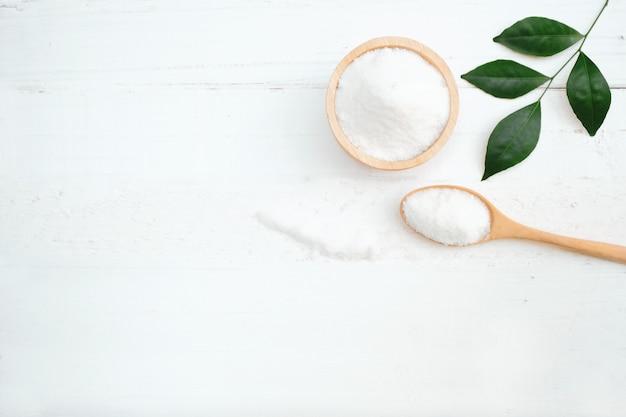 Lo zucchero è in una ciotola di legno posta su un tavolo bianco.