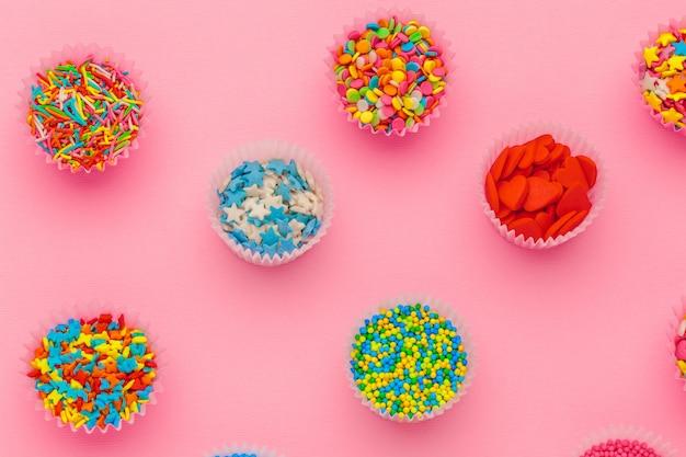 Lo zucchero spruzza, decorazione per torta e gelato e biscotti su sfondo rosa
