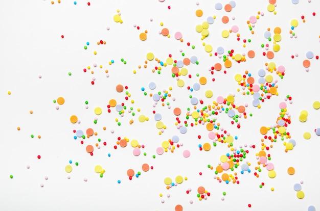 Lo zucchero spruzza i punti su fondo bianco. dolce decorazione per torte.