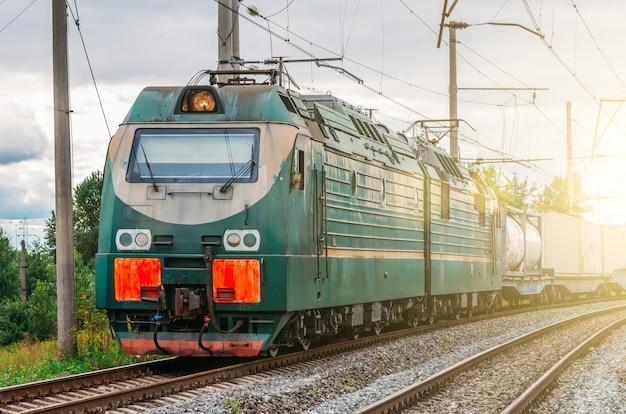 Locomotiva elettrica con un treno merci ad alta velocità su rotaia.