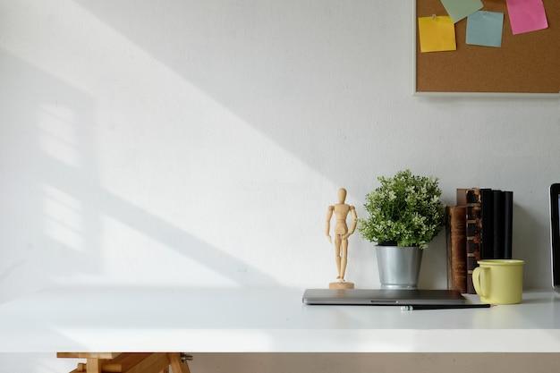 Loft di lavoro con libri d'epoca e forniture di design sul tavolo di legno bianco
