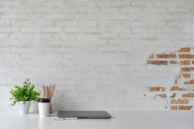 Loft di lavoro, copia spazio, laptop e materiali di consumo.