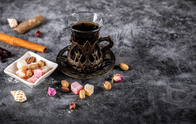 Lokum turco in un piattino bianco con un bicchiere di tè
