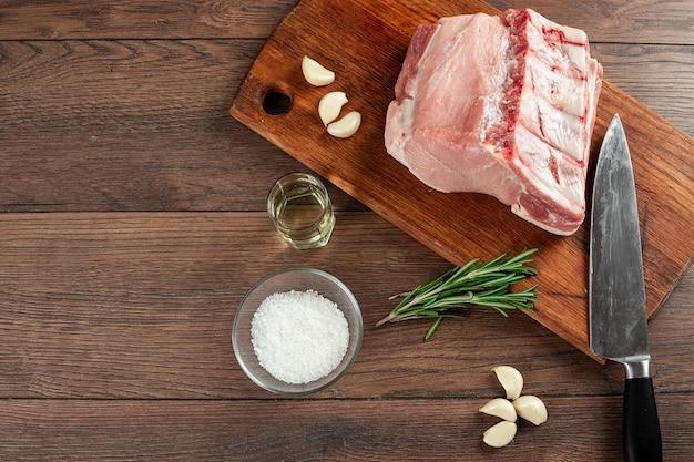 Lombo di bistecca fresco di carne cruda e spezie e un coltello si trova su legno.