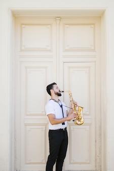 Long shot lateralmente musicista che suona il sassofono