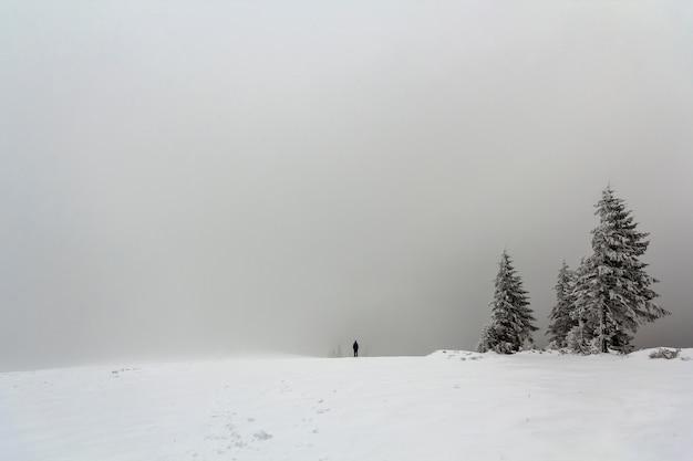 Lontano figura solitaria di un uomo in piedi all'aperto in inverno