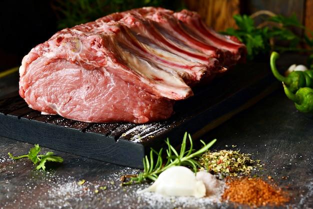 Lonza di maiale cruda fresca sull'osso su una tavola di legno con erbe, spezie e sale marino.