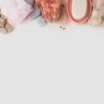 Loofah; pietra termale; salgemma rosa himalayano e sapone su sfondo bianco