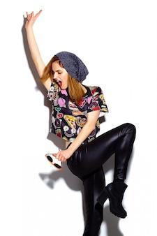 Look alla moda di alta moda modello alla moda della bella giovane donna con le labbra rosse in panno hipster in berretto che dà il segno del rock and roll