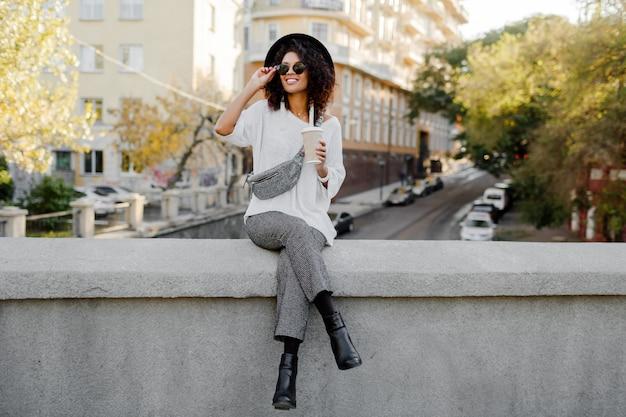 Look alla moda di strada. ragazza nera alla moda che si siede sul ponte e che tiene tazza di caffè o tè durante il suo tempo libero. donna freelance. indossa cappello nero e occhiali da sole.