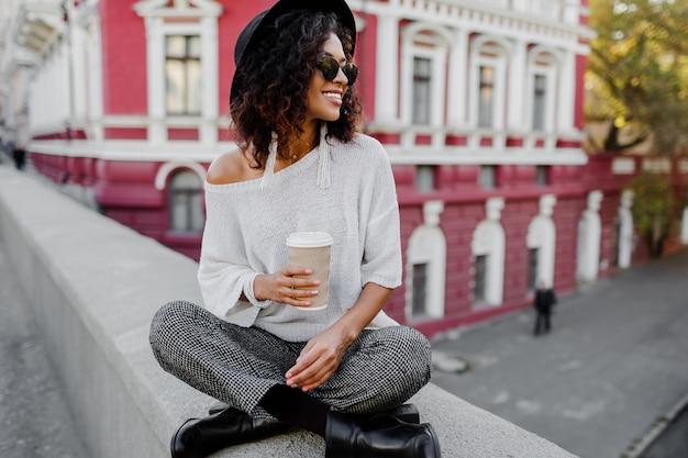 Look alla moda di strada. ragazza nera alla moda che si siede sul ponte e che tiene tazza di caffè