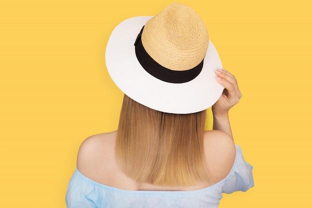 Look alla moda, modello di giovane donna in piedi indietro, indossa cappello e vestito blu su giallo