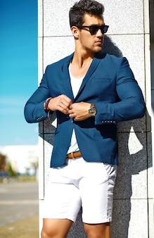 Look di alta moda. giovane uomo di modello di uomo d'affari bello felice fiducioso alla moda in vestito blu copre la strada in occhiali da sole dietro il cielo