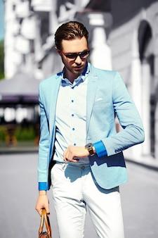 Look di alta moda. il giovane modello di uomo d'affari bello felice fiducioso alla moda in abito panno stile di vita in strada in occhiali da sole guarda il suo orologio