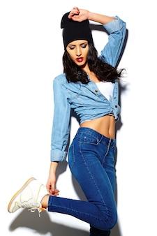 Look di alta moda look.glamor modello elegante bella giovane donna con labbra rosse in panno hipster hipster jeans colorati luminosi in berretto nero
