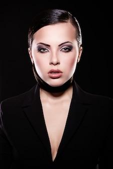 Look di alta moda. ritratto del modello di bella ragazza bruna in giacca nera con trucco luminoso e labbra succose. pelle pulita. isolato su nero