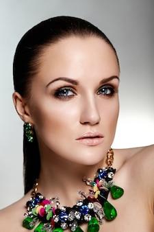 Look di alta moda. ritratto del primo piano di fascino di bello modello caucasico della giovane donna del brunette con capelli sani e monili accessori verdi