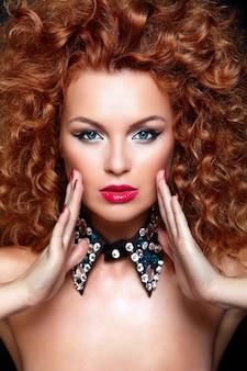 Look.glamor di alta moda closeup ritratto di bella sexy rossa caucasica giovane donna modello con labbra rosse, trucco luminoso, con una pelle pulita perfetta con gioielli isolato su nero