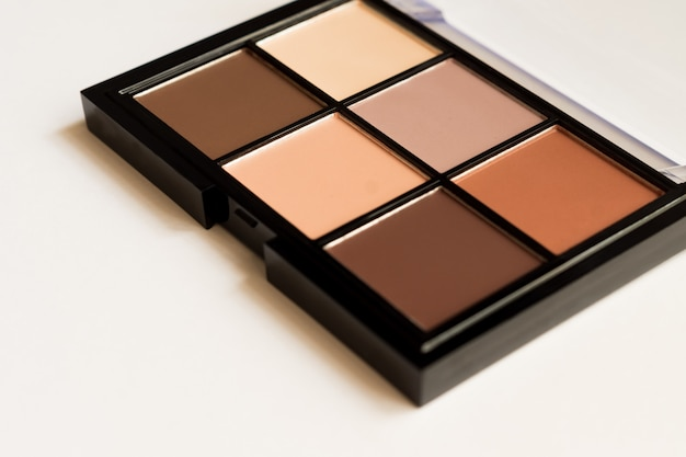 Look naturale, ombretti tono marrone compongono la tavolozza in custodia nera su sfondo bianco. messa a fuoco selettiva