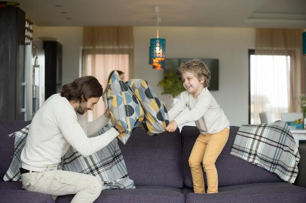 Lotta di cuscini tra padre e figlio piccolo nel soggiorno