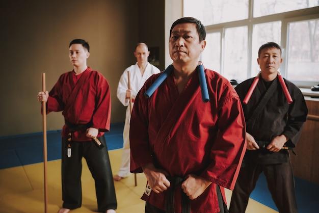 Lotta uomo in un kimono rosso è in piedi.
