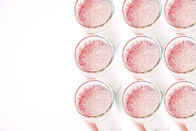 Lotti del primo piano e di vista superiore di tubo di vetro capillare medico in contenitore su fondo bianco., progettato sia per la raccolta sicura del sangue che per le accurate determinazioni di microematocrito precisione.