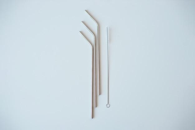 Lotto dei tubi del metallo per i cocktail con schutkoy per pulizia isolata su bianco.