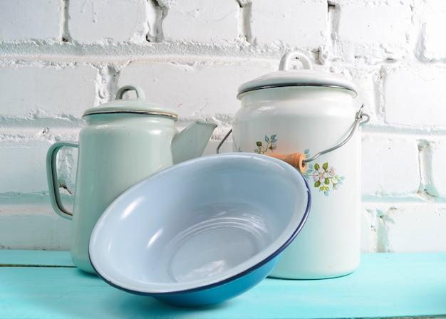 Lotto di piatti smaltati su un tavolo blu su sfondo bianco muro di mattoni. pentole in stile retrò