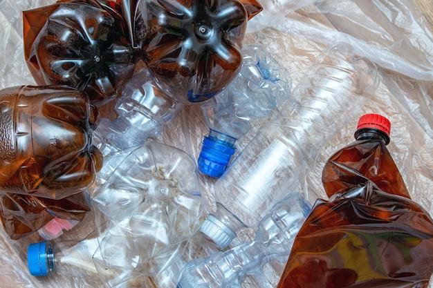 Lotto di plastica usata, bottiglie vuote sgualcite, pacchetti, l'inquinamento ricicla il concetto di eco