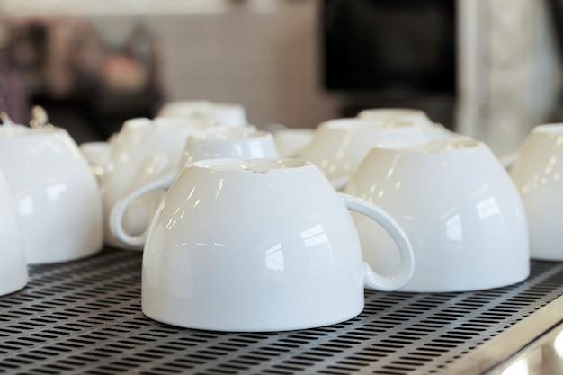 Lotto di tazze bianche pulite bianche nel ristorante dopo il lavaggio.
