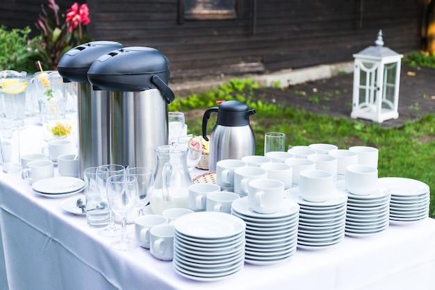 Lotto di tazze da caffè in porcellana bianca e grandi thermos sul tavolo in una festa estiva all'aperto