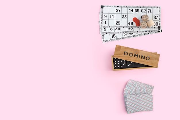 Lotto, domino e carte da gioco su una parete rosa, vista dall'alto. giochi da tavolo per la casa