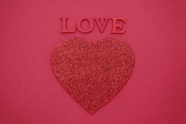 Love lettering, lettere rosse in legno 3d su rosso con cuore rosso. biglietto di auguri di san valentino